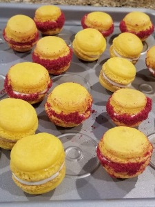 Mini lemon macarons, some with freeze-dried raspberry dust around edges