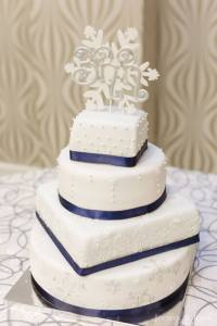 4-tier white wedding cake with navy ribbon and BRR snowflake cake topper