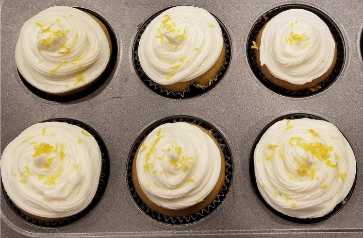 6 full-size cupcakes in cupcake tin decorated with piped frosting and lemon zest